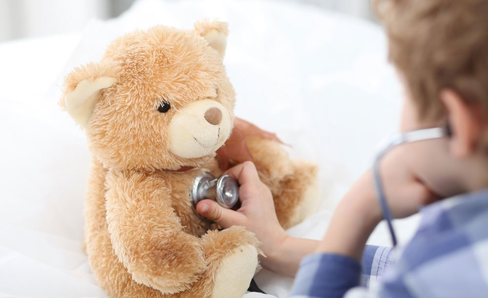 child playing doctor with a teddy bear